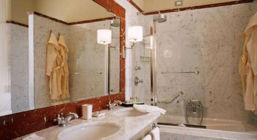 featuring a marble bathroom this elegant room is decorated with light colours room facilities safety deposit box air conditioning desk extra long beds